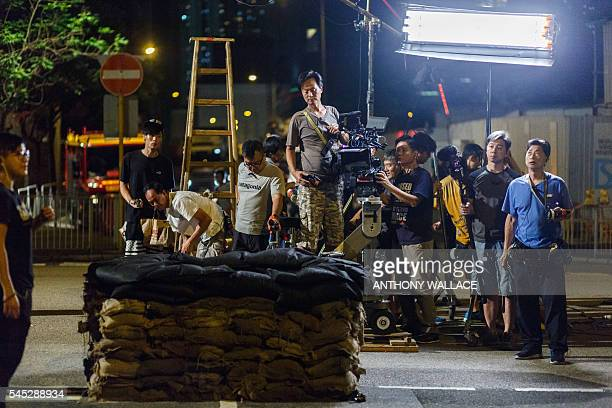 In this picture taken on May 23 members of a film crew working with local director Herman Yau prepare to film a scene for their movie Shock Wave in...