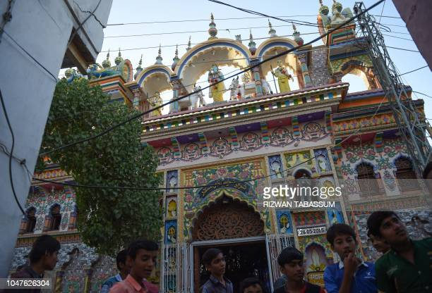 In this picture taken on May 24 children gather outside the Hindu Shri Krishna Temple in Mithi some 320 km from Karachi Cows roam freely in the...