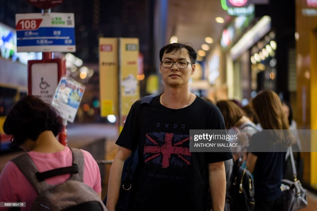 In this picture taken on May 24, 2017, Ken, a 27-year-old builder, poses while wearing a T-shirt with a British national flag design as he waits for his bus after work in Hong Kong. When asked whether he prefers Hong Kong before or after the 1997 handover from British to Chinese rule, he replied, 'I miss the times before 1997. Now high house prices, many mainland Chinese people in Hong Kong.' From its rattling trams and racecourses to its legal system and the ubiquitous consumption of Spam, Britain's colonial legacy still resonates through Hong Kong. But almost 20 years since the city was handed back to China under a deal that made it semi-autonomous, colonial emblems have become a symbol of protest. / AFP PHOTO / Anthony WALLACE / TO GO WITH Hong Kong-China-Britain-politics-history-culture-handover, FEATURE by Laura MANNERING