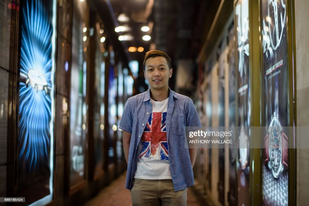 In this picture taken on May 24, 2017, Mingo, a 27-year-old bar manager, poses while wearing a T-shirt with a British national flag design in Hong Kong. When asked whether he prefers Hong Kong before or after the 1997 handover from British to Chinese rule, he replied, 'Before 1997, definitely. Because the Chinese government is taking over Hong Kong now. It's becoming part of China. I love the UK, that's why I bought the shirt. UK is my second family as I studied there for a long time. That's why I love the flag.' From its rattling trams and racecourses to its legal system and the ubiquitous consumption of Spam, Britain's colonial legacy still resonates through Hong Kong. But almost 20 years since the city was handed back to China under a deal that made it semi-autonomous, colonial emblems have become a symbol of protest. / AFP PHOTO / Anthony WALLACE / TO GO WITH Hong Kong-China-Britain-politics-history-culture-handover, FEATURE by Laura MANNERING