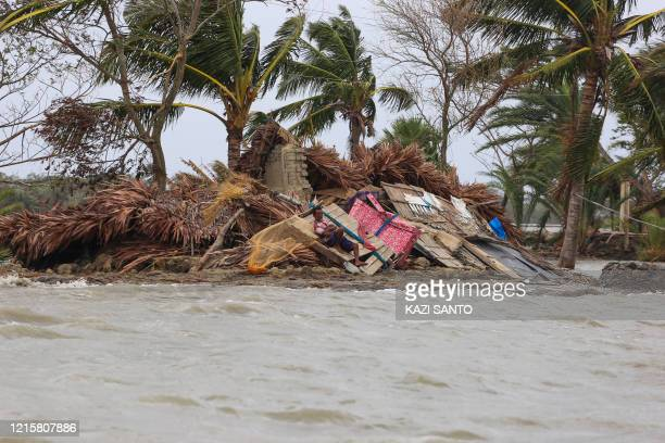 TOPSHOT In this picture taken on May 27 2020 a man rests laying on the debris of his home surrounded by floodwater a week after cyclone Amphan...