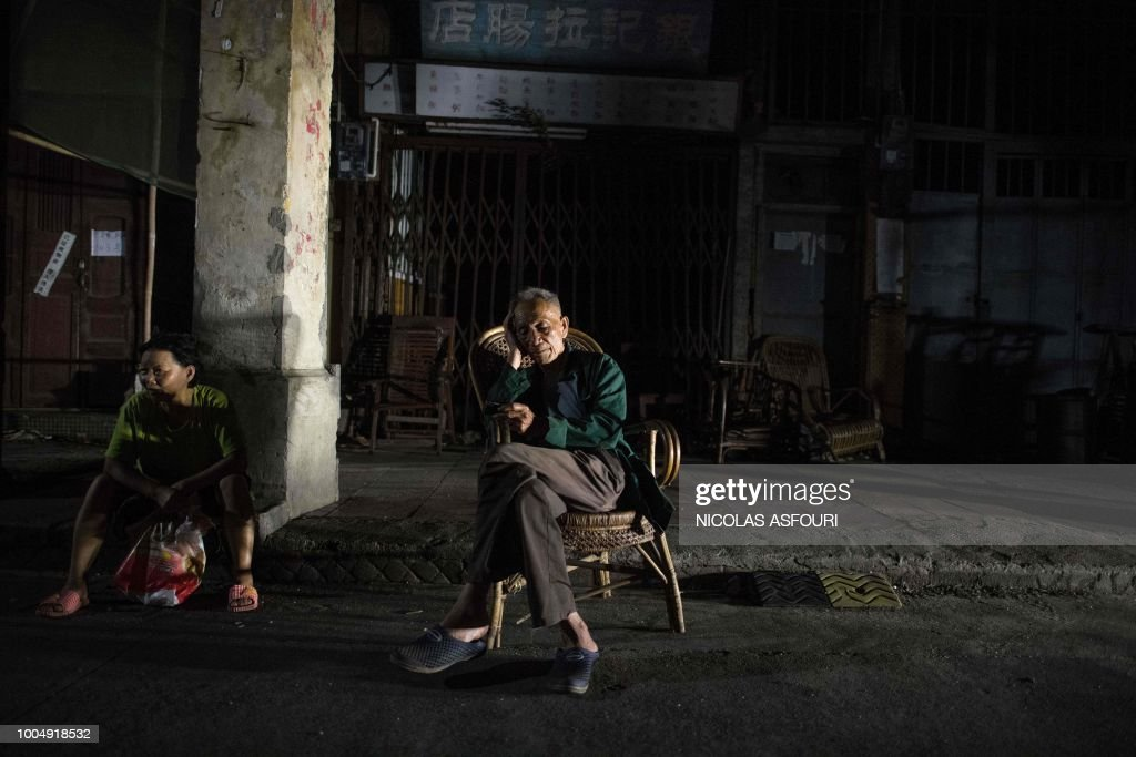 In this picture taken on May 28, 2018, an elderly man holding a portable radio listens to traditional Chinese songs as he sits on a chair along a street in Chikan village in Kaiping. - Several dozen inhabitants of a historic section of the town of Chikan in southern China are stubbornly holding out against government pressure to sell their properties to make way for a 'heritage' theme park. Chikan was listed as a UNESCO World Heritage Site in June 2007 due to its 19th- and early 20th-century houses, which feature a unique mix of European and Chinese architecture, clock towers and intricate stone wall carvings. (Photo by NICOLAS ASFOURI / AFP) / TO GO WITH China-migration-rights-tourism,FEATURE by Joanna Chiu