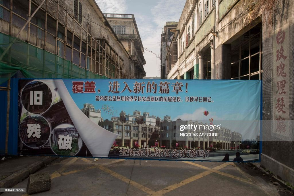 In this picture taken on May 29, 2018, a banner sealing off a street that reads 'covering up (the old), entering a new chapter!', is seen in Chikan village in Kaiping. - Several dozen inhabitants of a historic section of the town of Chikan in southern China are stubbornly holding out against government pressure to sell their properties to make way for a 'heritage' theme park. Chikan was listed as a UNESCO World Heritage Site in June 2007 due to its 19th- and early 20th-century houses, which feature a unique mix of European and Chinese architecture, clock towers and intricate stone wall carvings. (Photo by NICOLAS ASFOURI / AFP) / TO GO WITH China-migration-rights-tourism,FEATURE by Joanna Chiu