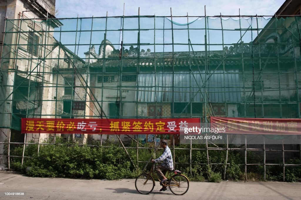In this picture taken on May 29, 2018, a cyclist rides past a banner that reads 'You will stand to lose if you ask sky-high prices but you will get benefit by signing the contract as soon as possible', in Chikan village in Kaiping. - Several dozen inhabitants of a historic section of the town of Chikan in southern China are stubbornly holding out against government pressure to sell their properties to make way for a 'heritage' theme park. Chikan was listed as a UNESCO World Heritage Site in June 2007 due to its 19th- and early 20th-century houses, which feature a unique mix of European and Chinese architecture, clock towers and intricate stone wall carvings. (Photo by NICOLAS ASFOURI / AFP) / TO GO WITH China-migration-rights-tourism,FEATURE by Joanna Chiu