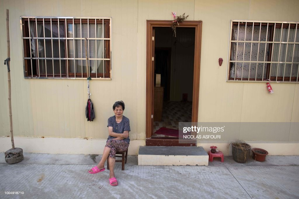 In this picture taken on May 29, 2018, a former resident of Chikan village sits outside her temporary government housing apartment in Kaiping. - Several dozen inhabitants of a historic section of the town of Chikan in southern China are stubbornly holding out against government pressure to sell their properties to make way for a 'heritage' theme park. Chikan was listed as a UNESCO World Heritage Site in June 2007 due to its 19th- and early 20th-century houses, which feature a unique mix of European and Chinese architecture, clock towers and intricate stone wall carvings. (Photo by NICOLAS ASFOURI / AFP) / TO GO WITH China-migration-rights-tourism,FEATURE by Joanna Chiu