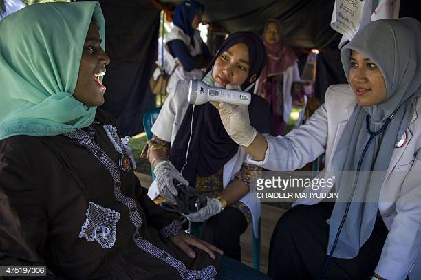 In this picture taken on May 29 a Indonesian medical personnel attend to a Rohingya woman from Myanmar at a confinement camp for rescued Rohingya...