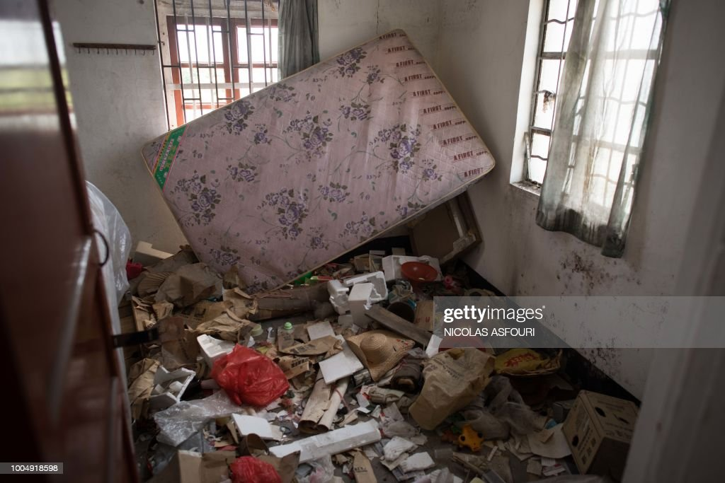 In this picture taken on May 29, 2018, a mattress and other items left behind by former residents are seen inside an apartment in Chikan village in Kaiping. - Several dozen inhabitants of a historic section of the town of Chikan in southern China are stubbornly holding out against government pressure to sell their properties to make way for a 'heritage' theme park. Chikan was listed as a UNESCO World Heritage Site in June 2007 due to its 19th- and early 20th-century houses, which feature a unique mix of European and Chinese architecture, clock towers and intricate stone wall carvings. (Photo by NICOLAS ASFOURI / AFP) / TO GO WITH China-migration-rights-tourism,FEATURE by Joanna Chiu