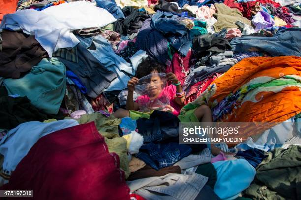 In this picture taken on May 29 a Rohingya migrant child from Myanmar plays on a pile of clothes donated by Indonesian residents at a confinement...