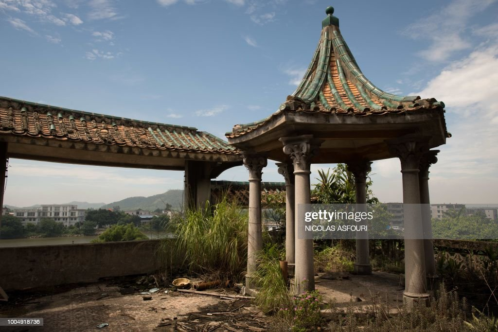In this picture taken on May 29, 2018, a view of the rooftop gazebo at the site of the old Situ family temple, which was seized during the Cultural Revolution and given to other villagers, is seen at Chikan village in Kaiping. - Several dozen inhabitants of a historic section of the town of Chikan in southern China are stubbornly holding out against government pressure to sell their properties to make way for a 'heritage' theme park. Chikan was listed as a UNESCO World Heritage Site in June 2007 due to its 19th- and early 20th-century houses, which feature a unique mix of European and Chinese architecture, clock towers and intricate stone wall carvings. (Photo by NICOLAS ASFOURI / AFP) / TO GO WITH China-migration-rights-tourism,FEATURE by Joanna Chiu