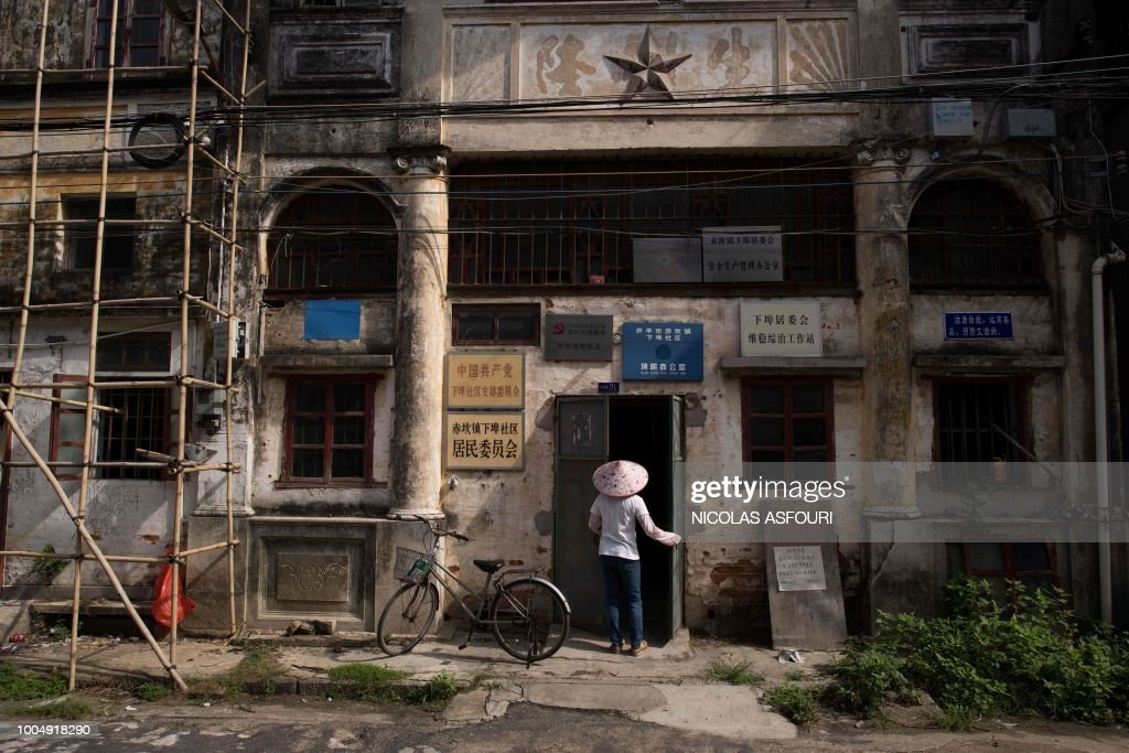 In this picture taken on May 29, 2018, a woman opens the door to an old government building in Chikan village in Kaiping. - Several dozen inhabitants of a historic section of the town of Chikan in southern China are stubbornly holding out against government pressure to sell their properties to make way for a 'heritage' theme park. Chikan was listed as a UNESCO World Heritage Site in June 2007 due to its 19th- and early 20th-century houses, which feature a unique mix of European and Chinese architecture, clock towers and intricate stone wall carvings. (Photo by NICOLAS ASFOURI / AFP) / TO GO WITH China-migration-rights-tourism,FEATURE by Joanna Chiu