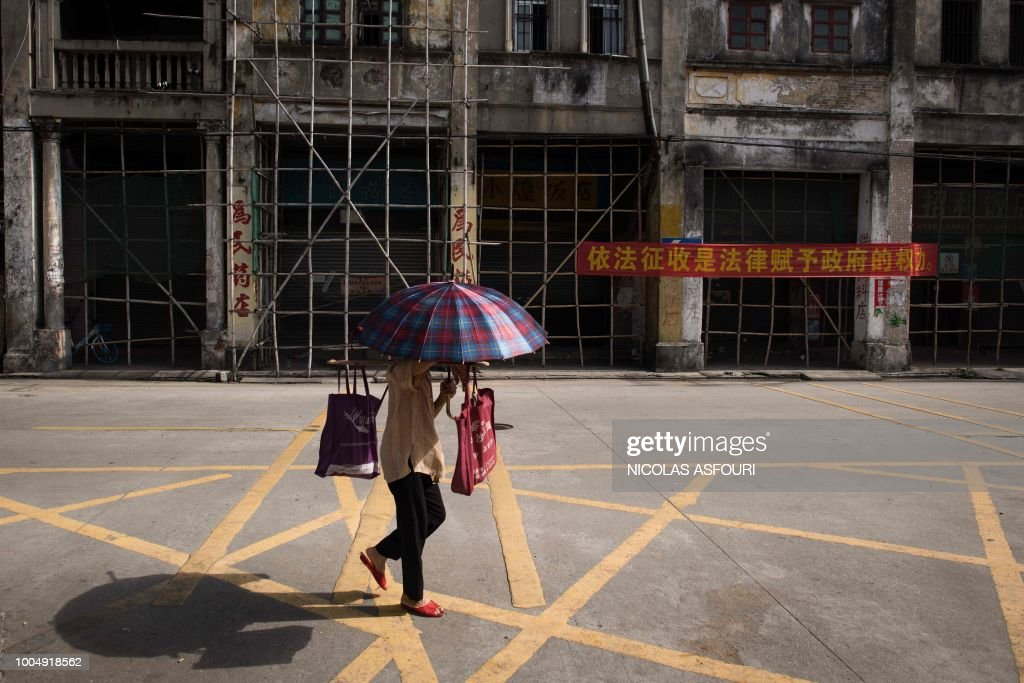 In this picture taken on May 29, 2018, an umbrella-toting pedestrian walks past a banner (R) that reads 'expropriation in accordance with the law is the right that the law gives the government', in Chikan village in Kaiping. - Several dozen inhabitants of a historic section of the town of Chikan in southern China are stubbornly holding out against government pressure to sell their properties to make way for a 'heritage' theme park. Chikan was listed as a UNESCO World Heritage Site in June 2007 due to its 19th- and early 20th-century houses, which feature a unique mix of European and Chinese architecture, clock towers and intricate stone wall carvings. (Photo by NICOLAS ASFOURI / AFP) / TO GO WITH China-migration-rights-tourism,FEATURE by Joanna Chiu