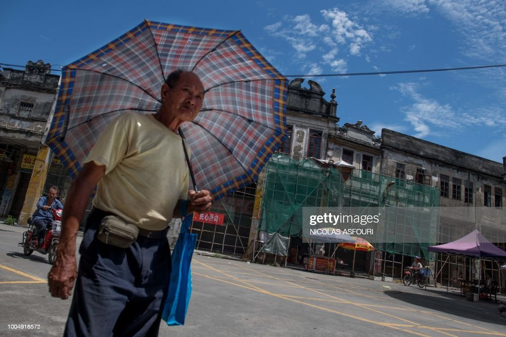 In this picture taken on May 29, 2018, an umbrella-toting pedestrian walks down a street on a hot day in Chikan village in Kaiping. - Several dozen inhabitants of a historic section of the town of Chikan in southern China are stubbornly holding out against government pressure to sell their properties to make way for a 'heritage' theme park. Chikan was listed as a UNESCO World Heritage Site in June 2007 due to its 19th- and early 20th-century houses, which feature a unique mix of European and Chinese architecture, clock towers and intricate stone wall carvings. (Photo by NICOLAS ASFOURI / AFP) / TO GO WITH China-migration-rights-tourism,FEATURE by Joanna Chiu