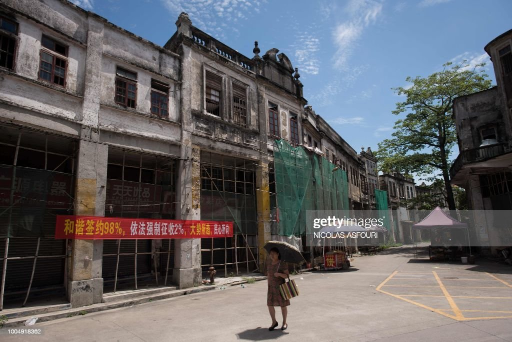 In this picture taken on May 29, 2018, an umbrella-toting pedestrian walks past rows of historic buildings in Chikan village in Kaiping. - Several dozen inhabitants of a historic section of the town of Chikan in southern China are stubbornly holding out against government pressure to sell their properties to make way for a 'heritage' theme park. Chikan was listed as a UNESCO World Heritage Site in June 2007 due to its 19th- and early 20th-century houses, which feature a unique mix of European and Chinese architecture, clock towers and intricate stone wall carvings. (Photo by NICOLAS ASFOURI / AFP) / TO GO WITH China-migration-rights-tourism,FEATURE by Joanna Chiu