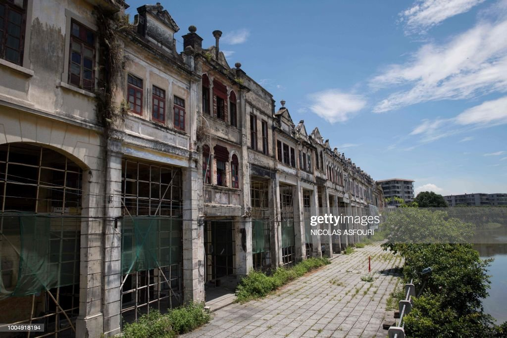In this picture taken on May 29, 2018, buildings and shops are seen in Chikan village in Kaiping. - Several dozen inhabitants of a historic section of the town of Chikan in southern China are stubbornly holding out against government pressure to sell their properties to make way for a 'heritage' theme park. Chikan was listed as a UNESCO World Heritage Site in June 2007 due to its 19th- and early 20th-century houses, which feature a unique mix of European and Chinese architecture, clock towers and intricate stone wall carvings. (Photo by NICOLAS ASFOURI / AFP) / TO GO WITH China-migration-rights-tourism,FEATURE by Joanna Chiu