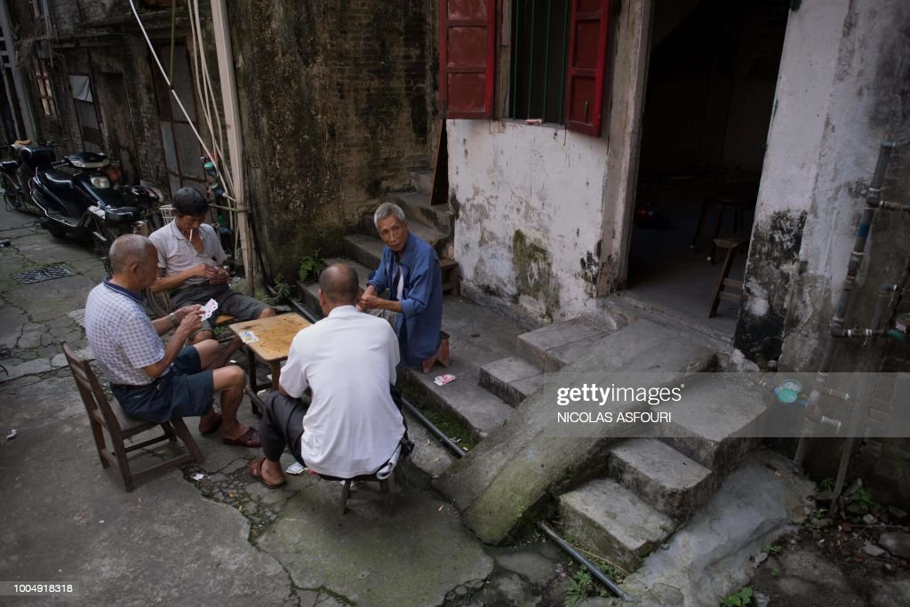 In this picture taken on May 29, 2018, local residents play cards on a street in Chikan village in Kaiping. - Several dozen inhabitants of a historic section of the town of Chikan in southern China are stubbornly holding out against government pressure to sell their properties to make way for a 'heritage' theme park. Chikan was listed as a UNESCO World Heritage Site in June 2007 due to its 19th- and early 20th-century houses, which feature a unique mix of European and Chinese architecture, clock towers and intricate stone wall carvings. (Photo by NICOLAS ASFOURI / AFP) / TO GO WITH China-migration-rights-tourism,FEATURE by Joanna Chiu