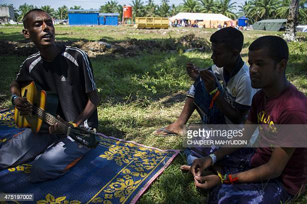 In this picture taken on May 29 migrant men from Bangladesh play music at a confinement camp for rescued Rohingya migrants from Myanmar and...
