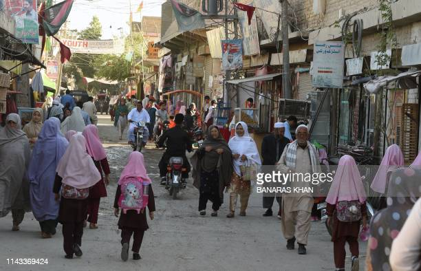 In this picture taken on May 3 Pakistani Shiite Hazara minority Muslims walk along a road in Hazara town a neighbourhood in Quetta Crowded into...