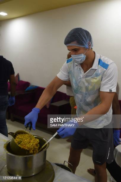 In this picture taken on May 6, 2020 Moldovan tennis player Dmitrii Baskov packs food to be distributed to people in need at the Ace Tennis Academy...