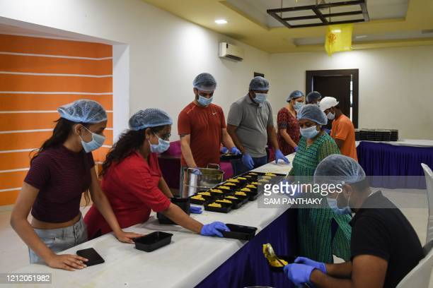 In this picture taken on May 6, 2020 volunteers of the Shri Sava Foundation pack food to be distributed to people in need during nationwide lockdown...