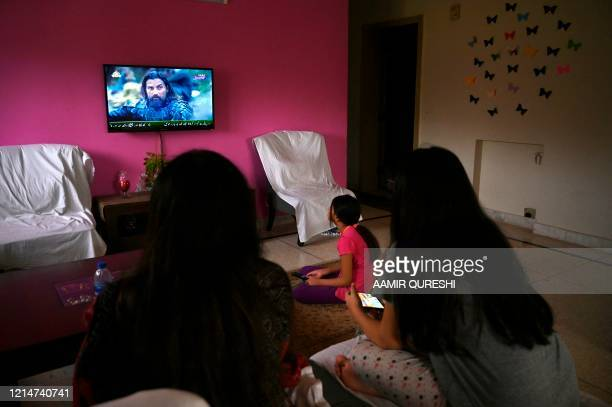 """In this picture taken on May 9 a family watches a Turkish drama series """"Dirilis: Ertugrul"""" telecasted on Pakistan's state-run channel PTV Home during..."""