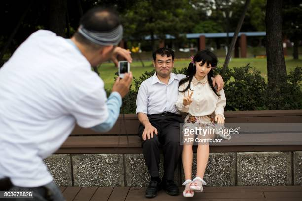TOPSHOT In this picture taken on May 9 a man takes pictures of physiotherapist Masayuki Ozaki and his silicone sex doll Mayu in Tokyo Bay Around 2000...