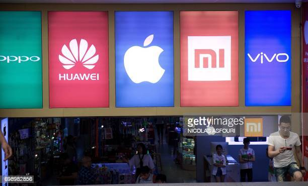 In this picture taken on May 9 a man using a phone walks past the logos of five smartphone companies including Chinese smartphone maker Oppo outside...