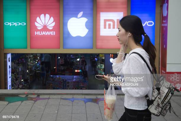 In this picture taken on May 9 a woman using a smartphone walks past the logos of five smartphone companies outside a smartphone shop in Shenzhen...
