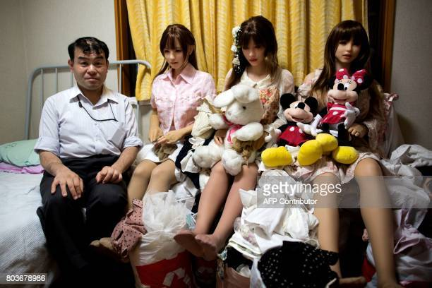 TOPSHOT In this picture taken on May 9 physiotherapist Masayuki Ozaki poses with his silicone sex dolls at his bedroom in Tokyo Around 2000 of the...