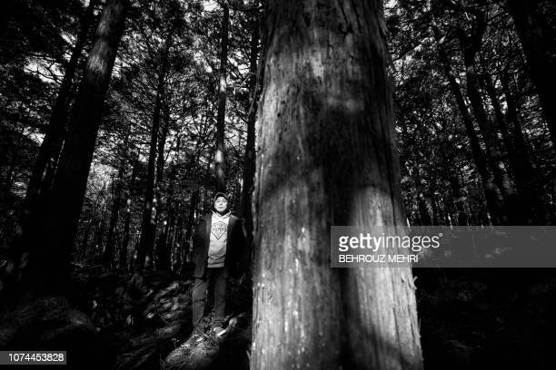In this picture taken on November 1 2018 Japanese musician Kyochi Watanabe poses for a photo in Aokigahara Forest known as Suicide Forest in Narusawa...