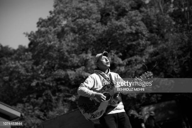 In this picture taken on November 1 2018 Japanese musician Kyochi Watanabe plays his guitar as he poses for a photo at the entrance of Aokigahara...