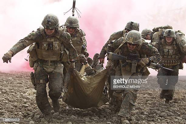 In this picture taken on November 10 2011 and cleared on December 202011 by the US Army US Marines carry a wounded comrade who was hit by an...