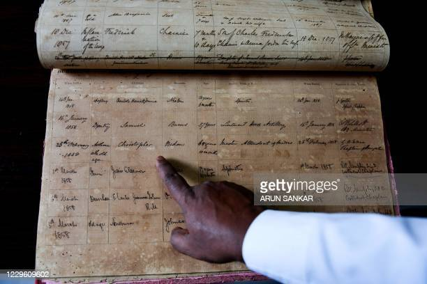 In this picture taken on November 10 a pastor shows the burial record of Christoper Biden, a potential ancestor of US President-elect Joe Biden, at a...