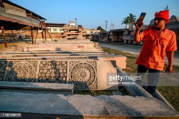 In this picture taken on November 12 a devotee takes video with his mobile phone of stone slabs earmarked for the construction of a Hindu God Ram...