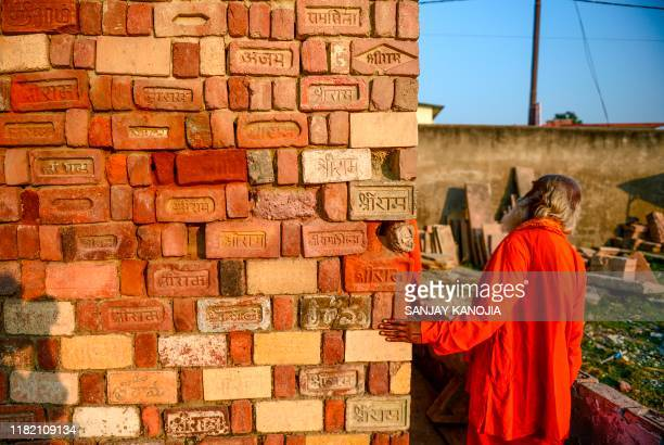 In this picture taken on November 12 a Sadhu looks at bricks for the proposed Rama temple Ram Janmabhoomi Nyas workshop in Ayodhya after the Supreme...