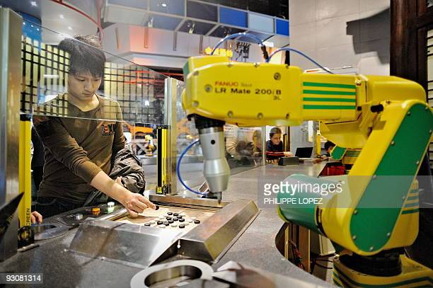 In this picture taken on November 13 2009 a visitor plays a Chinese chess game against a robot at the Science and Technology Museum in Shanghai...