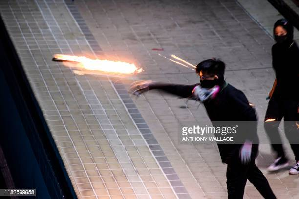 In this picture taken on November 14 a protester practices throwing a molotov cocktail into an emptied 50metre Olympicsize swimming pool at the Hong...