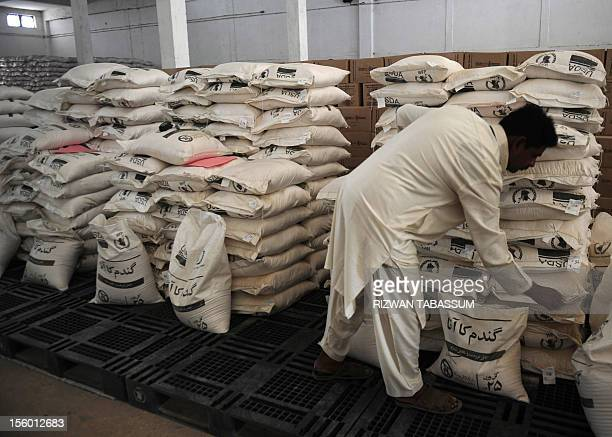 In this picture taken on November 2 a Pakistani worker arranges aid supplies at the World Food Programme supply centre at Mirali Village in Jacobabad...
