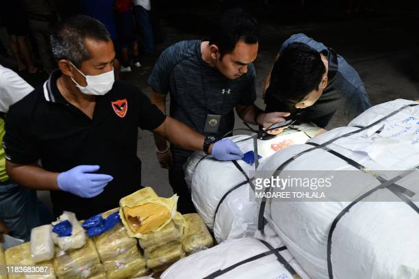 In this picture taken on November 20 police officers inspect pacakges of methamphetamine pills which were transported by truck from northern Thailand...