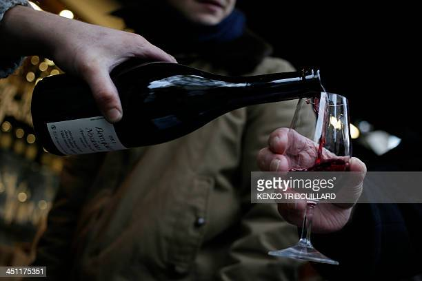 In this picture taken on November 21 wine growers pour wine during the traditional Beaujolais Nouveau 2013 edition in Paris From the heart of France...