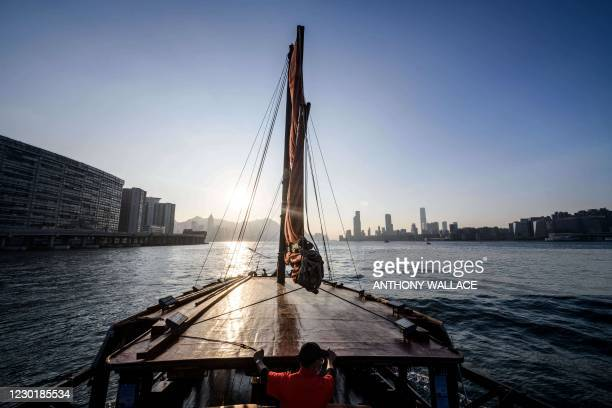 """In this picture taken on November 27 a deckhand sails on a traditional wooden tourist junk boat """"Dukling"""" in Hong Kong, which was built in 1955 in..."""