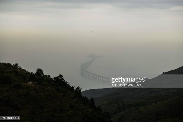 In this picture taken on November 29 a passenger jet flies over a section of the Hong KongZhuhaiMacau Bridge in Hong Kong Billed as the world's...