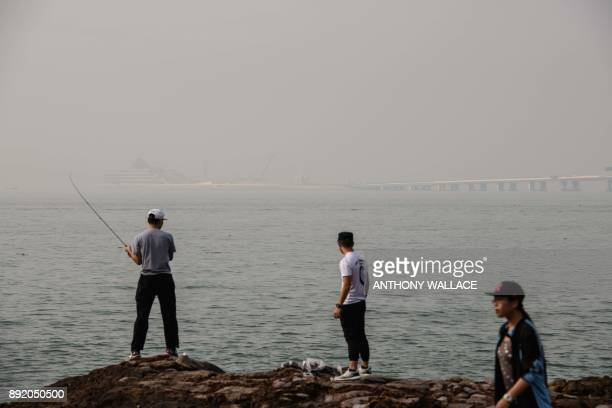 In this picture taken on November 29 an angler fishes off the Lantau fishing village of Tai O which overlooks the Hong KongZhuhaiMacau Bridge in Hong...