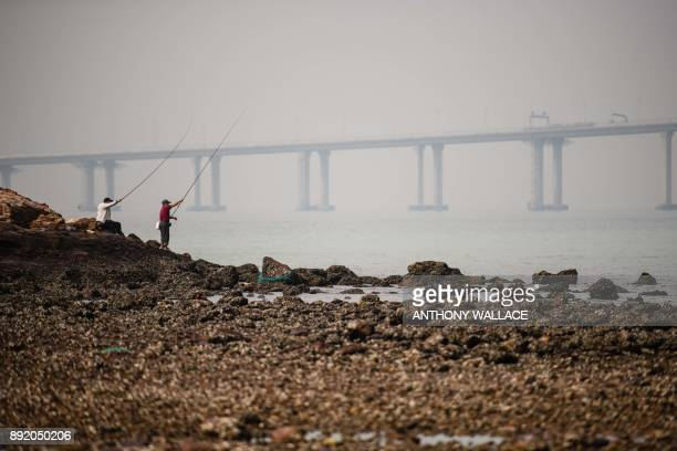In this picture taken on November 29 anglers fish off the Lantau fishing village of Tai O, which overlooks the Hong Kong-Zhuhai-Macau Bridge in Hong...