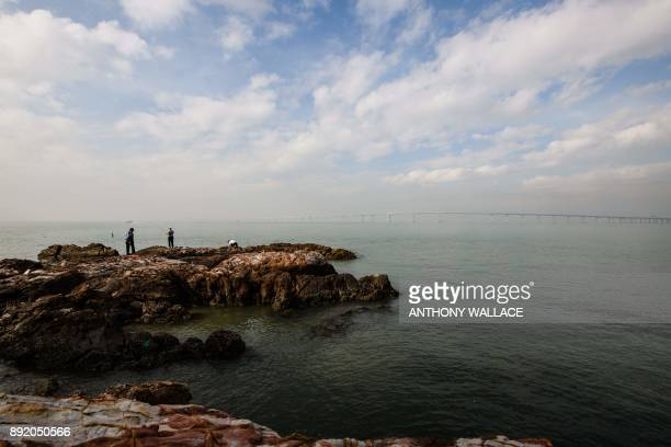 In this picture taken on November 29 anglers fish off the Lantau fishing village of Tai O which overlooks the Hong KongZhuhaiMacau Bridge in Hong...