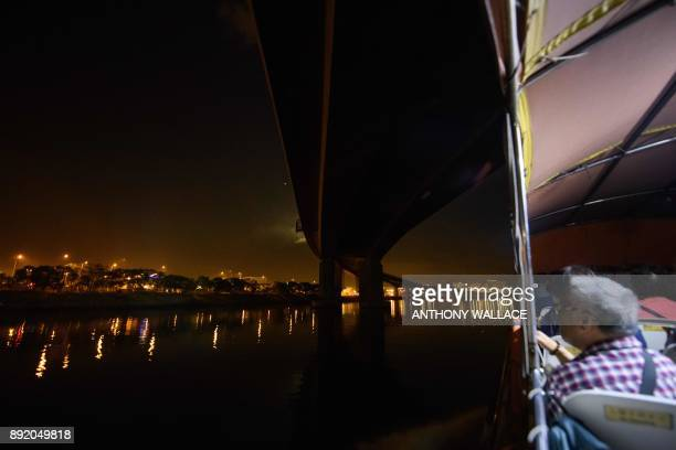 In this picture taken on November 29 commuters on a ferry go underneath a section of the Hong KongZhuhaiMacau Bridge in Hong Kong Billed as the...
