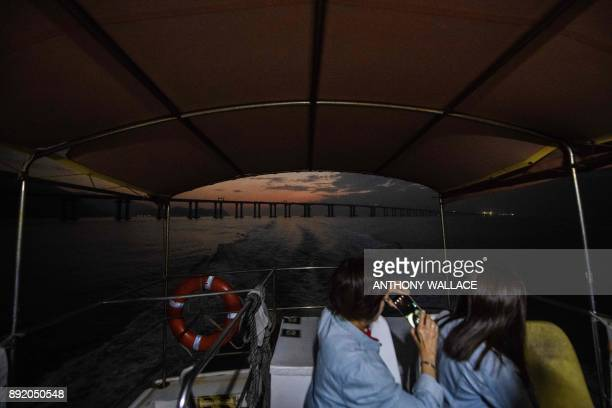 In this picture taken on November 29 commuters on a ferry take photos of a section of the Hong KongZhuhaiMacau Bridge in Hong Kong Billed as the...