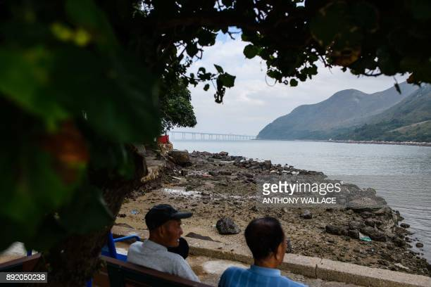 In this picture taken on November 29 two friends chat as they sit on a bench in the Lantau fishing village of Tai O which overlooks the Hong...