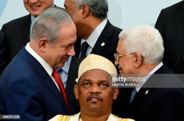 In this picture taken on November 30 2015 Israeli Prime Minister Benjamin Netanyahu talks with Palestine's president Mahmud Abbas behind Comoros'...