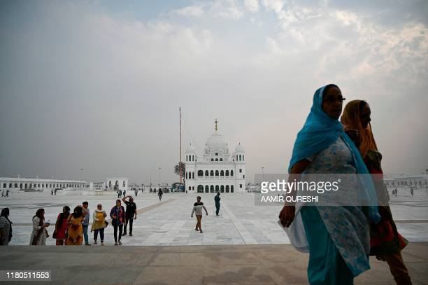 In this picture taken on November 6 2019 Sikh pilgrims walk in front of the Shrine of Baba Guru Nanak Dev at the Gurdwara Darbar Sahib ahead of its...
