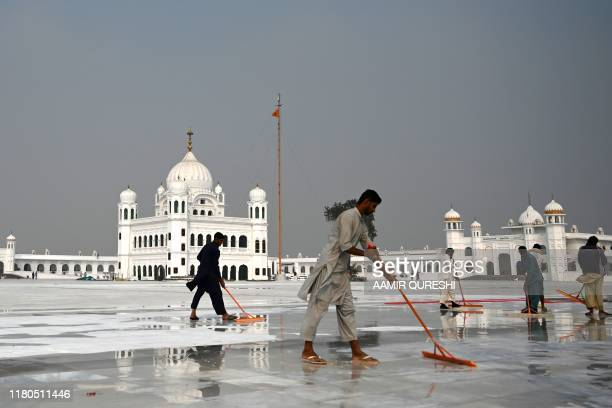 In this picture taken on November 6 2019 workers clean the floor at the Shrine of Baba Guru Nanak Dev at the Gurdwara Darbar Sahib ahead of its...